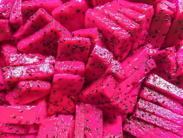 Спелые сочные кусочки розовой питайи. тропический фруктовый фон дракона.