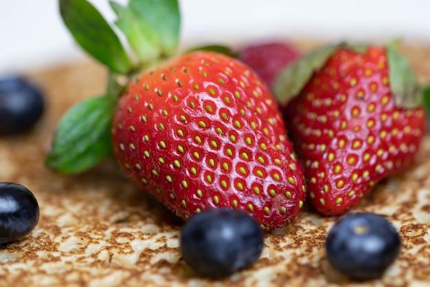 熟したジューシーなイチゴとブルーベリーが美味しいパンケーキの上に横たわっています。新鮮なベリーを使ったロシア料理の郷土料理のブリヌイ。