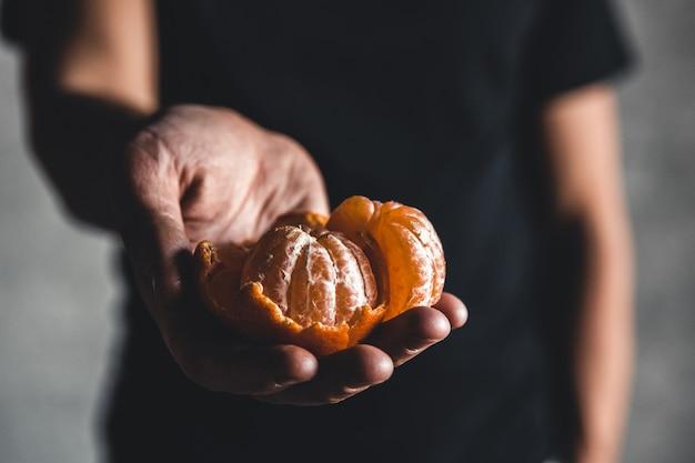 Спелые сочные сладкие оранжевые мандарины в человеческой руке на темном фоне. pnov2019