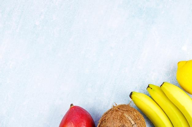 Ripe juicy tropical summer seasonal fruits mango  coconut kiwi bananas strawberries on yellow background. v