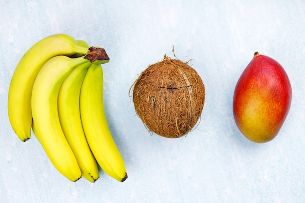 Ripe juicy tropical summer seasonal fruits mango  coconut kiwi bananas strawberries on yellow background.