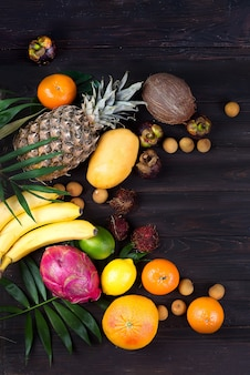 Ripe juicy tropical summer seasonal fruits on palm leaf on wooden background.