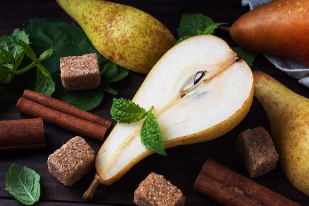 木製の背景にシナモンと熟したジューシーな黄色の梨。カラメル化のためのコンファレンスナシ。