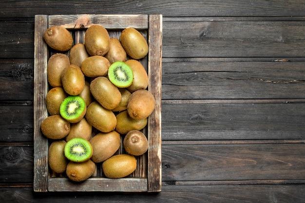 시골 풍 테이블에 나무 쟁반에 잘 익은 키위 과일