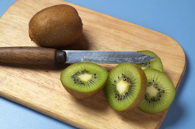 熟したキウイフルーツと木製キッチンボード上のスライス