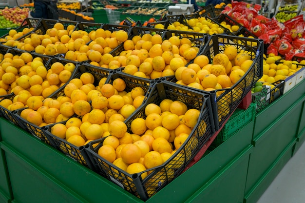Ripe lemons in boxes on the shelves of a supermarket
