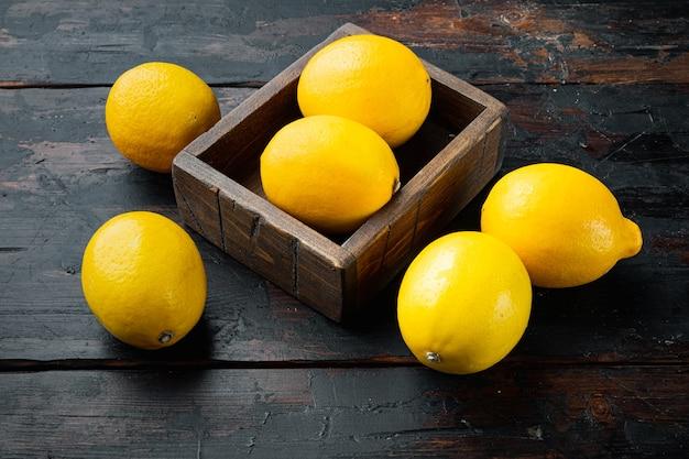 Набор спелых лимонов, в деревянной коробке, на темном деревянном фоне