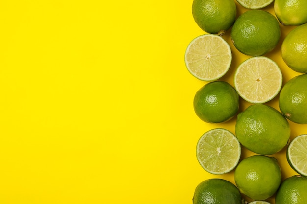 Ripe lime on yellow background, space for text