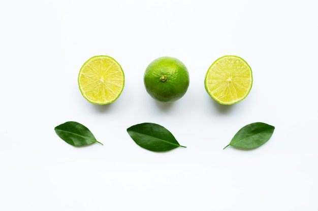 Ripe limes with green leaves on white.