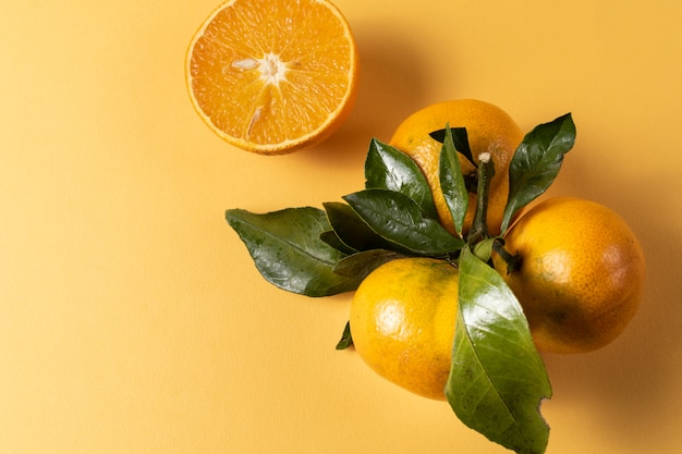 Ripe mandarin or tangerine fruit with green leaves over yellow background.