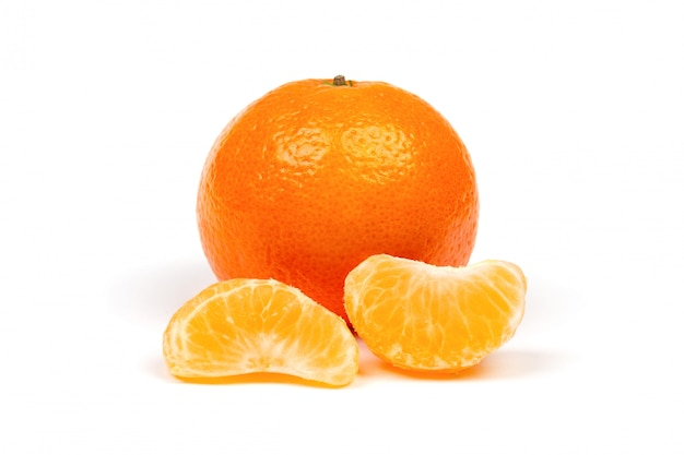 Ripe mandarine in peel and peeled tangerine slices close-up isolated