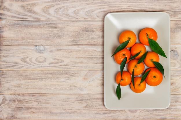 Зрелый мандарин с листьями, апельсин мандарина на предпосылке деревянного стола с космосом экземпляра.