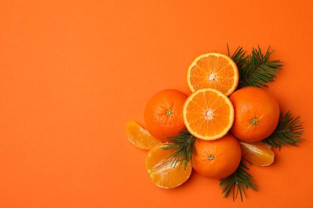 オレンジ色の熟したみかんと松の枝