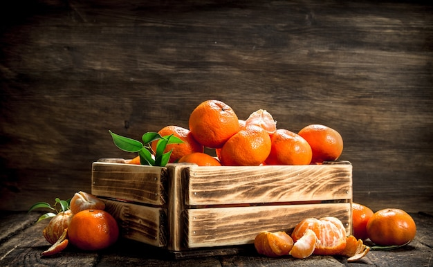 Ripe mandarins in an old box on a wooden background