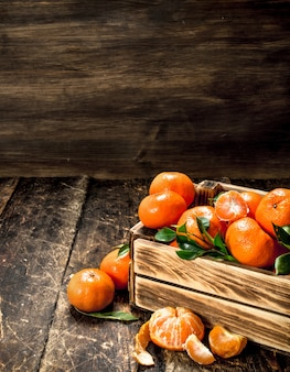 Ripe mandarins in an old box on wooden table.
