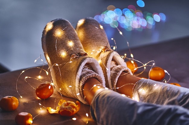 Спелые оранжевые мандарины, теплые белые гирлянды из рождественских огней и женские ножки в теплых пушистых мягких зимних тапочках в уютном доме в канун рождества