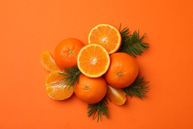 Ripe mandarins and pine branches on orange