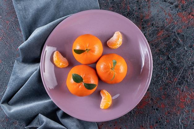 Mandarini maturi con foglie poste su un piatto viola