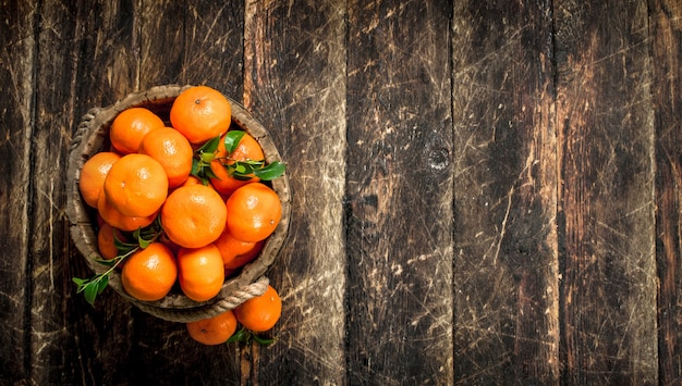 Ripe mandarins in a wooden bucket on a wooden background