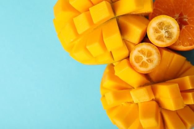Спелое манго и апельсин на синем фоне.