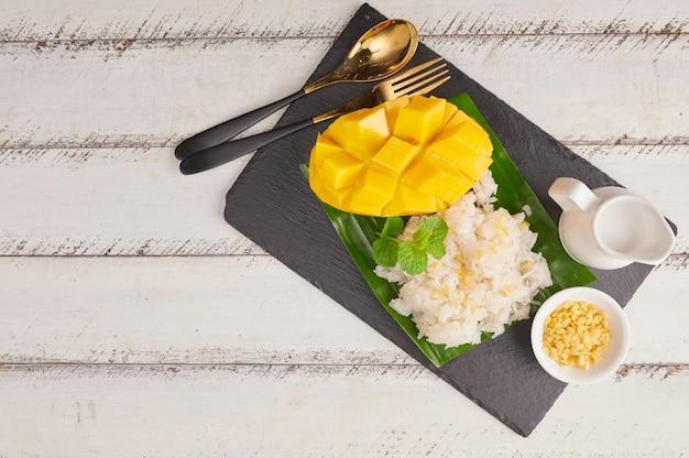 Спелое манго и липкий рис с кокосовым молоком на каменной поверхности, тайский сладкий десерт в летний сезон. Бесплатные Фотографии