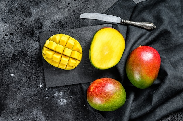 Ripe mango fruit, cut into cubes. black background.