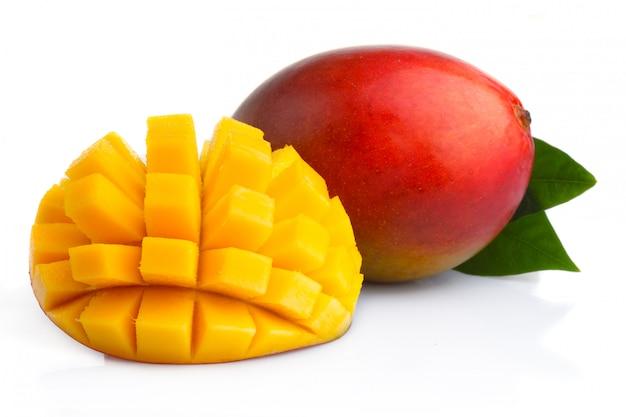 白で隔離されるスライスと熟したマンゴーフルーツ