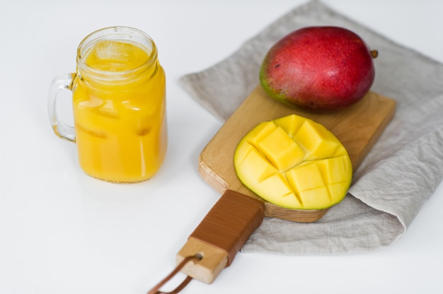 Ripe mango and a glass of mango juice on a wooden chopping board.