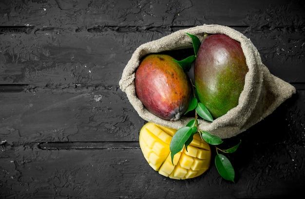 袋の中の熟したマンゴー。黒の素朴な背景に