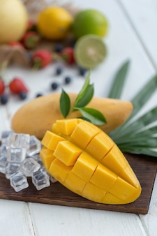 Ripe Mango on a wooden plate with ice cubes and fruit as background