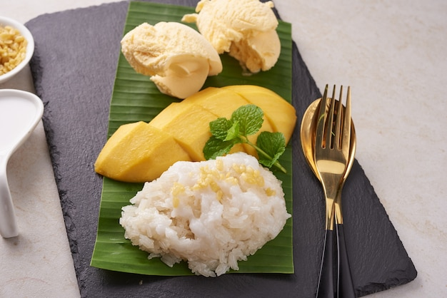 Ripe mango and sticky rice, ice cream with coconut milk on stone surface, thai sweet dessert on summer season. tropical fruit.  dessert fruit. top view.