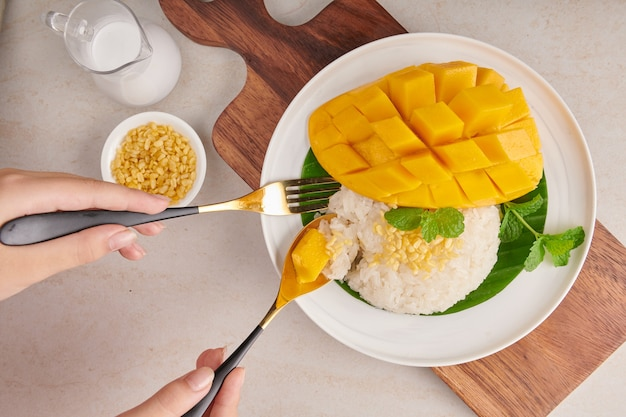 Ripe mango and sticky rice with coconut milk in a plate on stone surface, thai sweet dessert on summer season. woman hands with fork and spoon eating mango and sticky rice. top view.