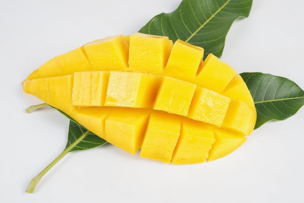 Ripe mango with green leaf of mango on white background, cut in cubes