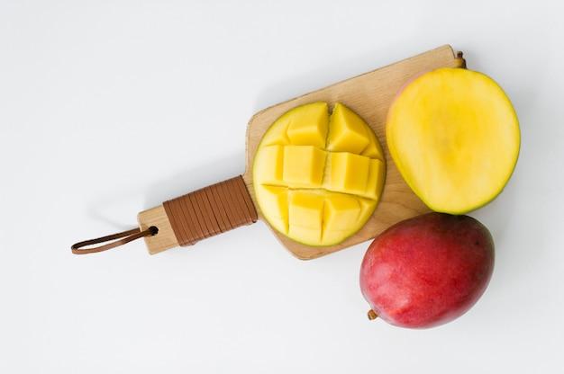 Ripe mango on the wooden cutting board.