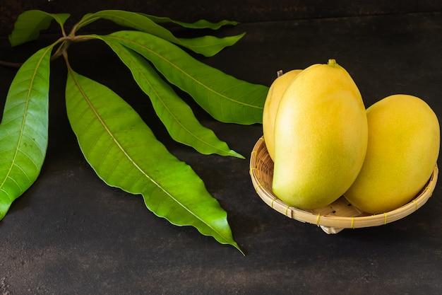 いくつかの葉の近くのバスケットで熟したマンゴー