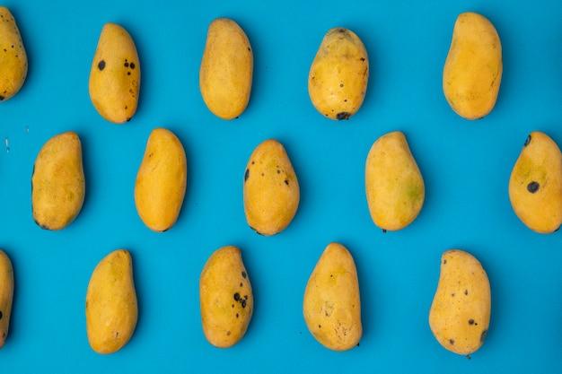 青い背景にパターンで配置された熟したマニラマンゴー