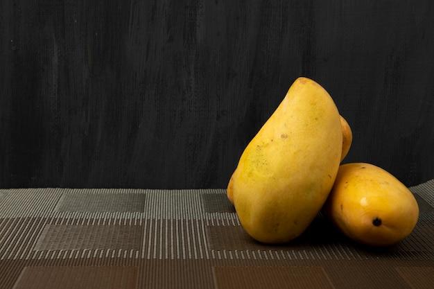 黒の背景と茶色のマットに熟したマニラマンゴー