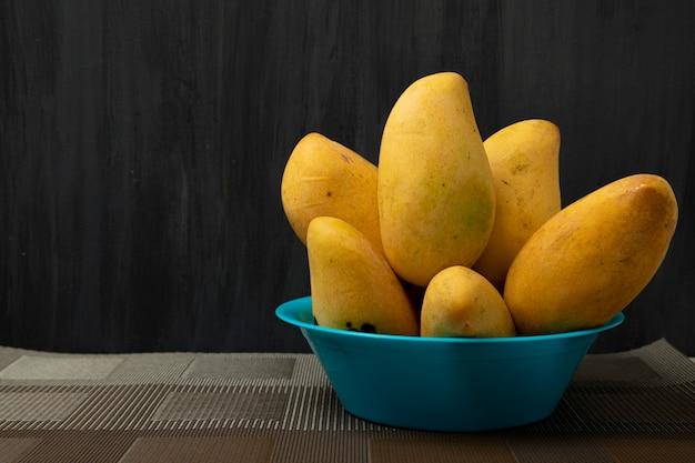 黒の背景と青いプレート上の熟したマニラマンゴー