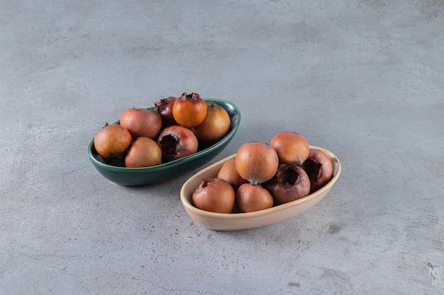 잘 익은 메들라 과일은 돌 표면에 놓여 있습니다.