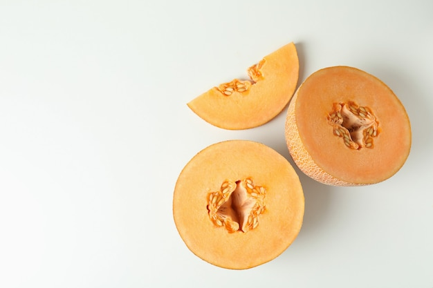 Ripe melon slices on white background, top view