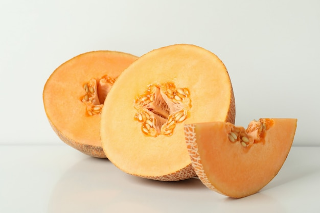 Ripe melon slices on white table, close up