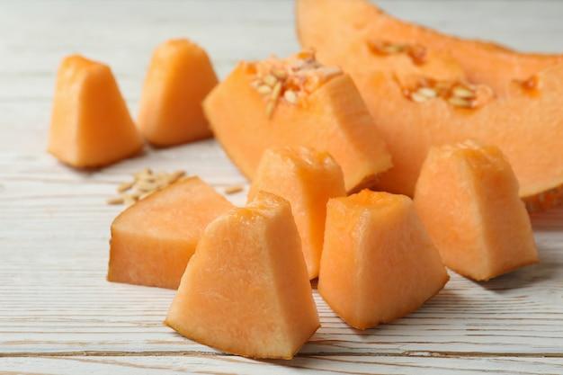 Ripe melon slices on white wooden background