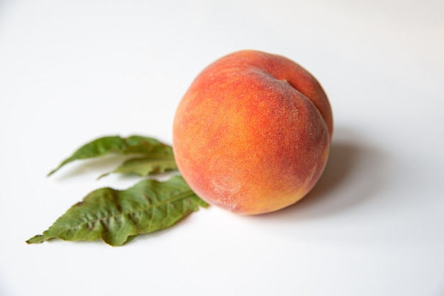 白いテーブルの上に葉を持つ熟した天然桃季節の果物とダイエットの概念を健康的に食べる