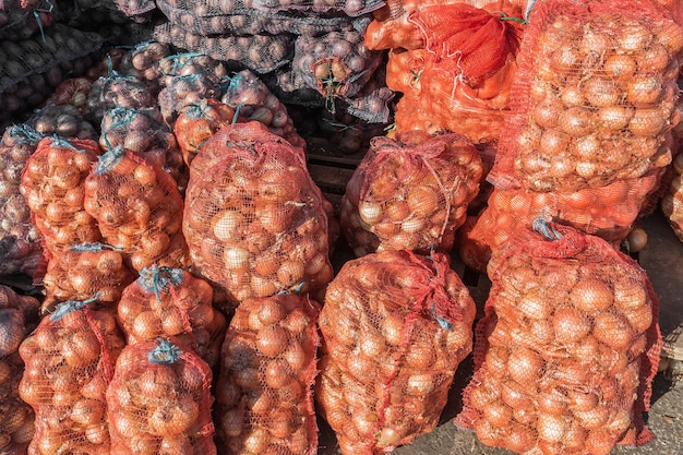 Ripe onions and potatoes in nets are sold at the vegetable market natural food products