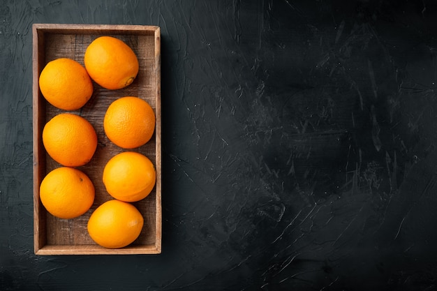 Ripe orange fruit set, in wooden box, on black stone table, top view flat lay