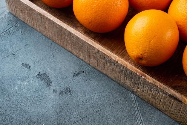 Ripe orange fruit set, in wooden box, on gray stone table
