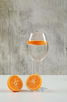 Спелые половинки апельсина с дольками апельсина в стакане воды, вид сбоку на шероховатой и белой поверхности