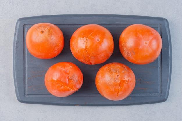 熟したオレンジ色の柿の果実。木の板に新鮮な柿。