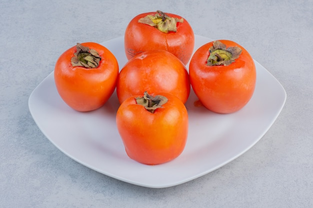 白い皿に熟したオレンジ色の柿の果実。