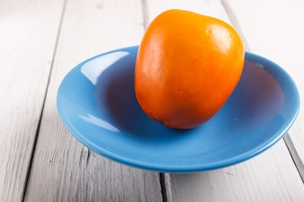 白い木製の背景に青い皿に熟したオレンジ色の柿